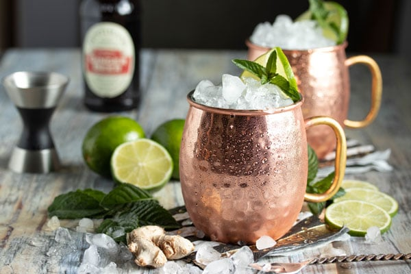 two moscow mule cups with cocktails inside.  A jigger in the background with some lime.