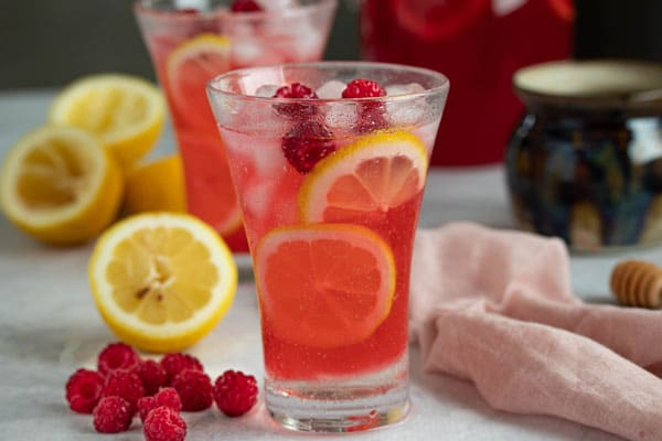 a raspberry cocktail with slices of lemons showing through the cocktail and raspberries on top