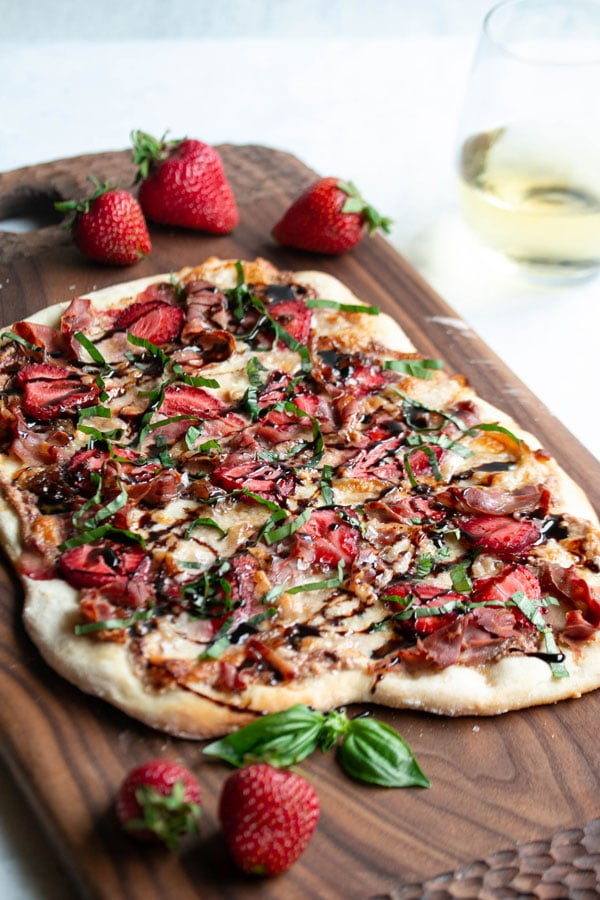 a strawberry pizza with basil and balsamic vinegar drizzled all over the top of it