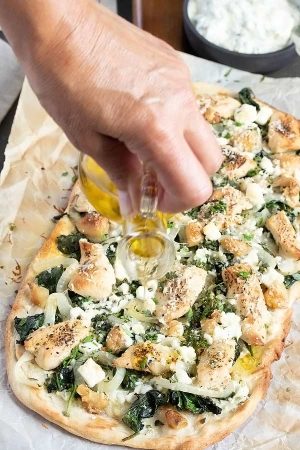 a hand pouring some olive oil on top of the greek chicken flatbread