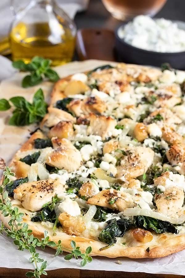 a greek flatbread pizza with chunks of chicken, spinach and onions on top.  Right out of the oven.
