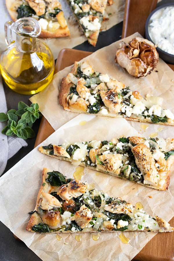three triangles of greek flatbread pizza with olive oil drizzled on top!