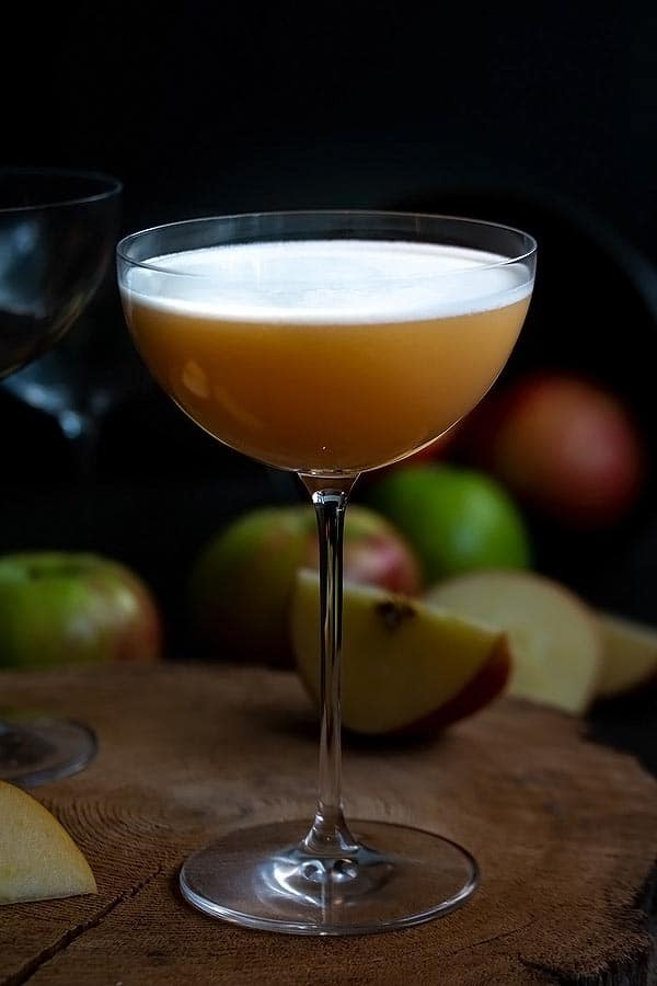 an apple whiskey sour in a martini glass with apples behind the glass