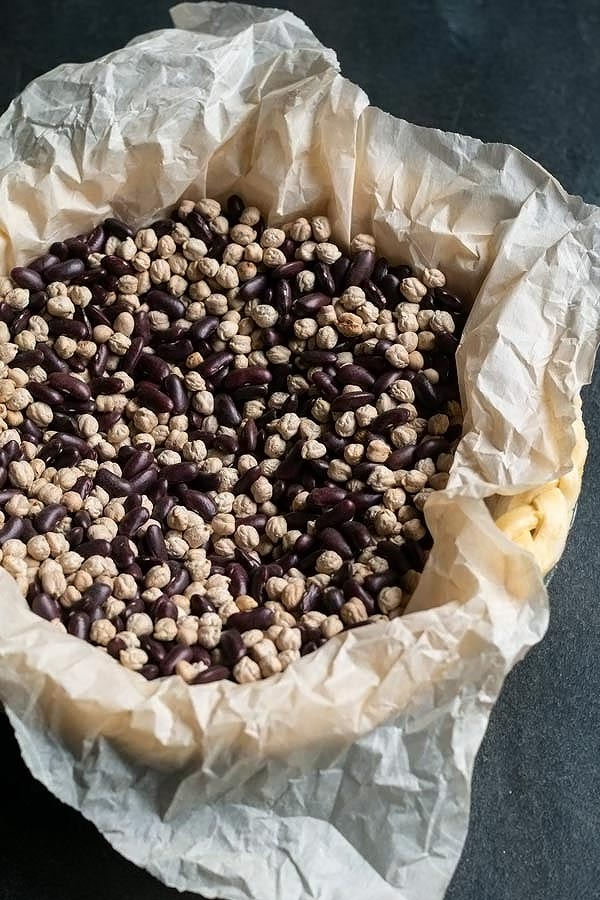 an unbaked pie crust with pie weights or dried beans in it