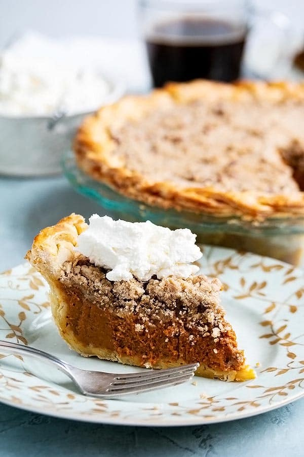 a slice of streusel pumpkin pie with whipped cream on top