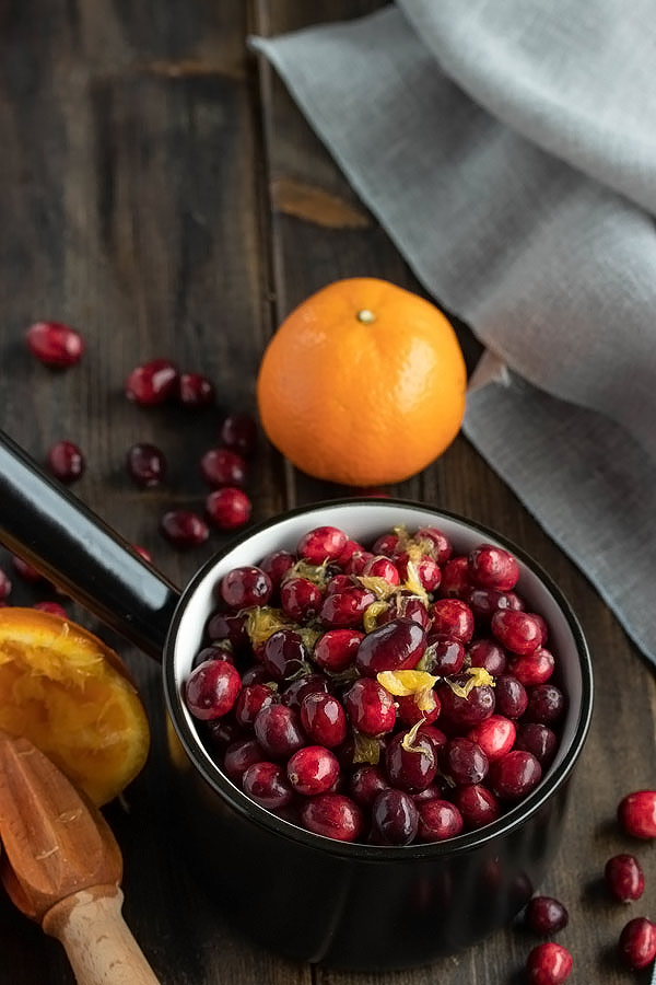 a pot of fresh cranberries with orange pulp on top from fresh orange juice