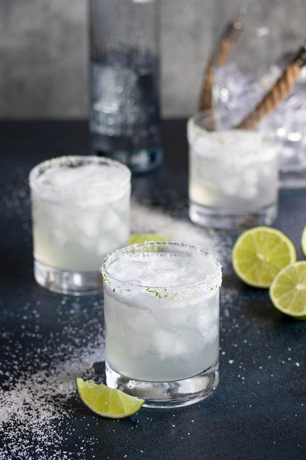 Three lime margaritas with frothy tops in glasses rimmed with salt and lime zest