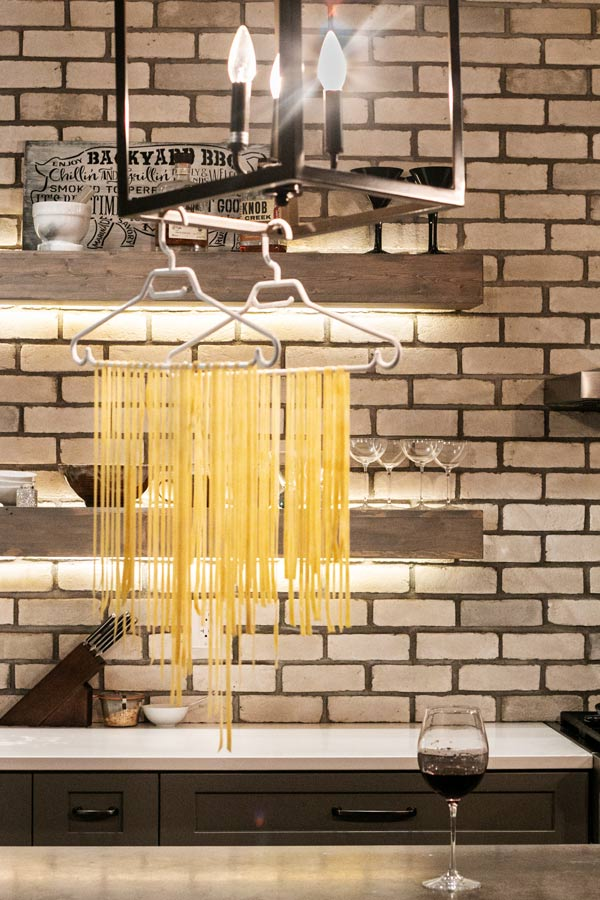 pasta noodles draped over a clothes hanger and hung by a light in the kitchen to dry