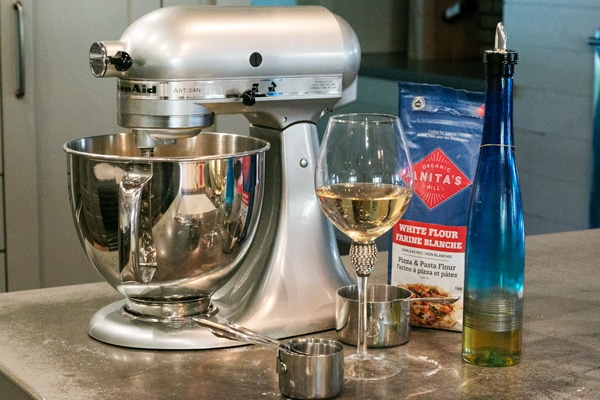 a kitchen aid mixer, pasta flour, oil and a glass of wine. I am ready to make pasta!