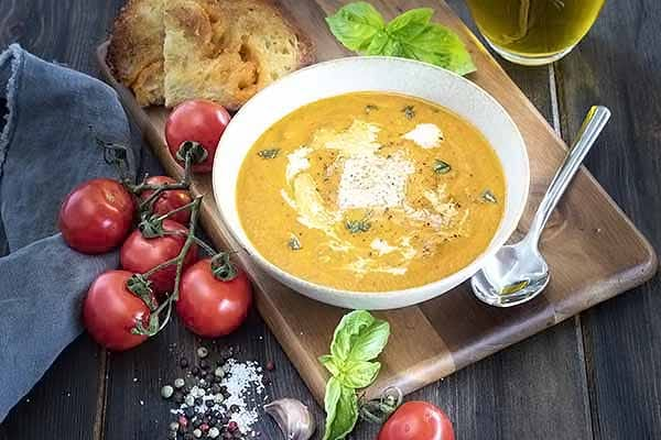 A bowl of tomato soup with a spoon and a toasted sourdough bread