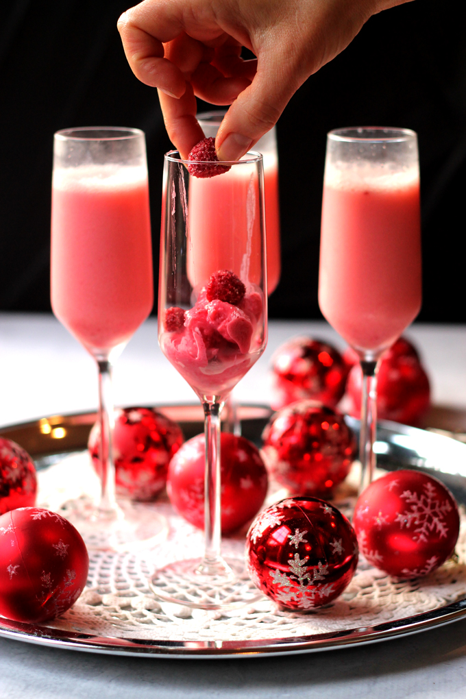 dropping a fresh raspberry in a champagne flute for a mimosa cocktail