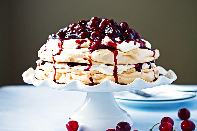 two layered pavlova with whipped cream in the middle and top and cherry compote on top