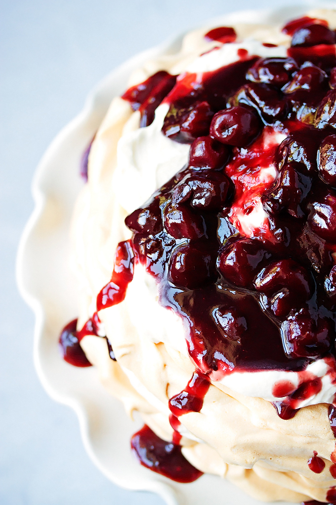looking down at the pavlova where the cherry compote is on top and drizzling over the sides
