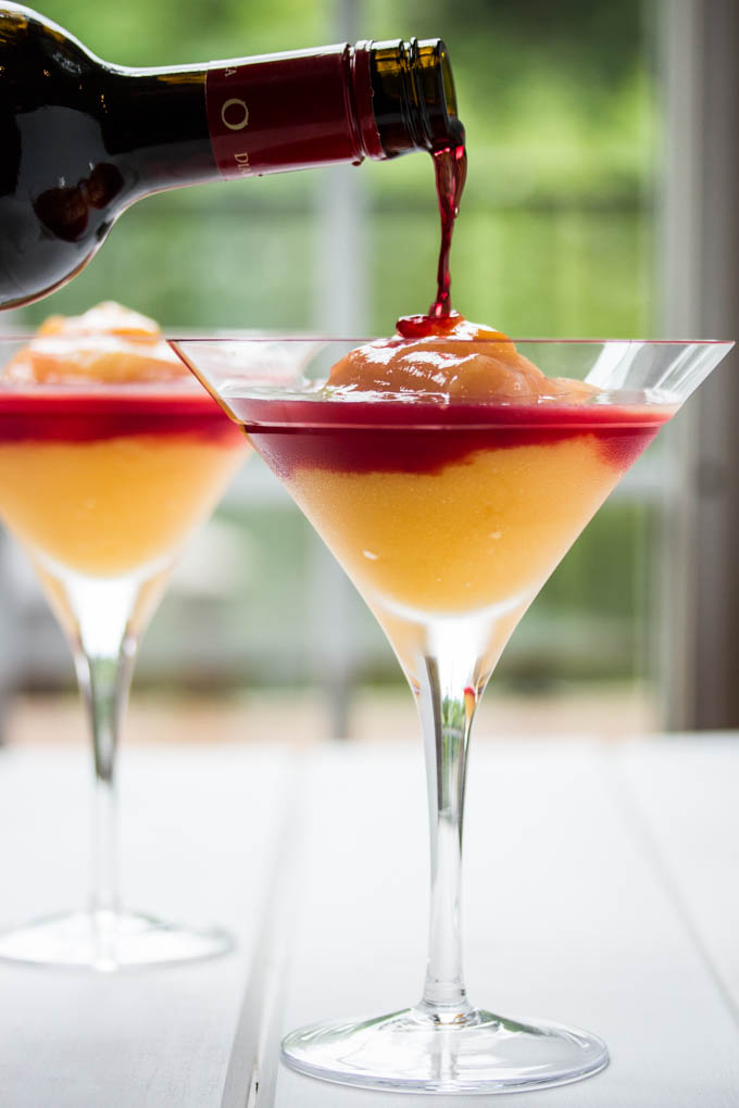 pouring wine to top off this peach bellini recipe